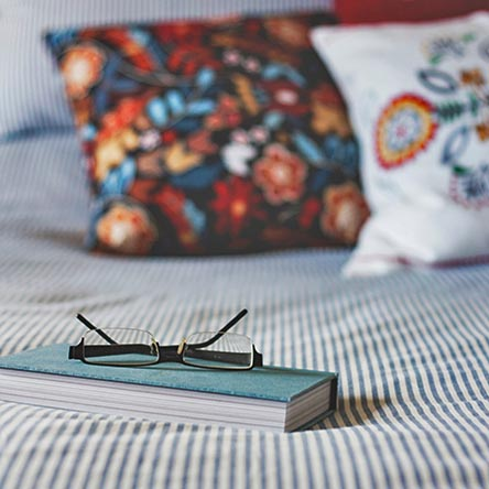 book-and-glasses-on-bed